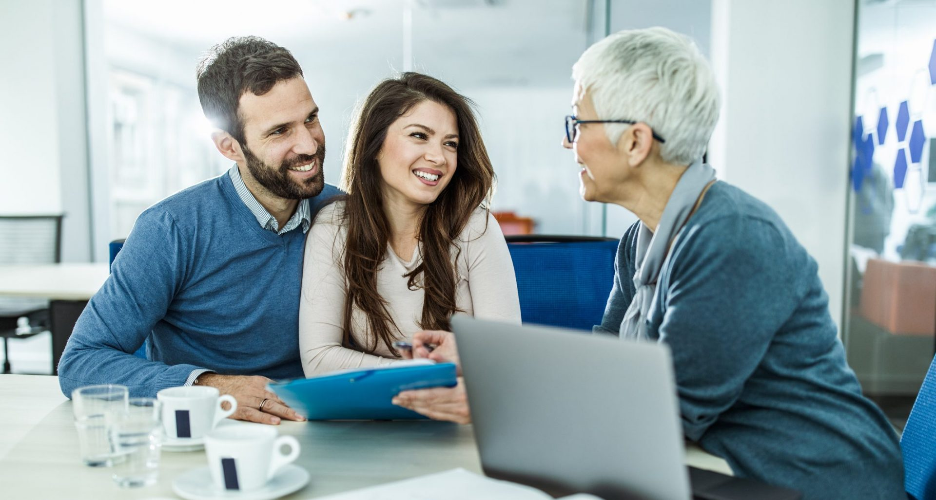 Young happy couple communicating with their mature financial advisor on a meeting in the office.
