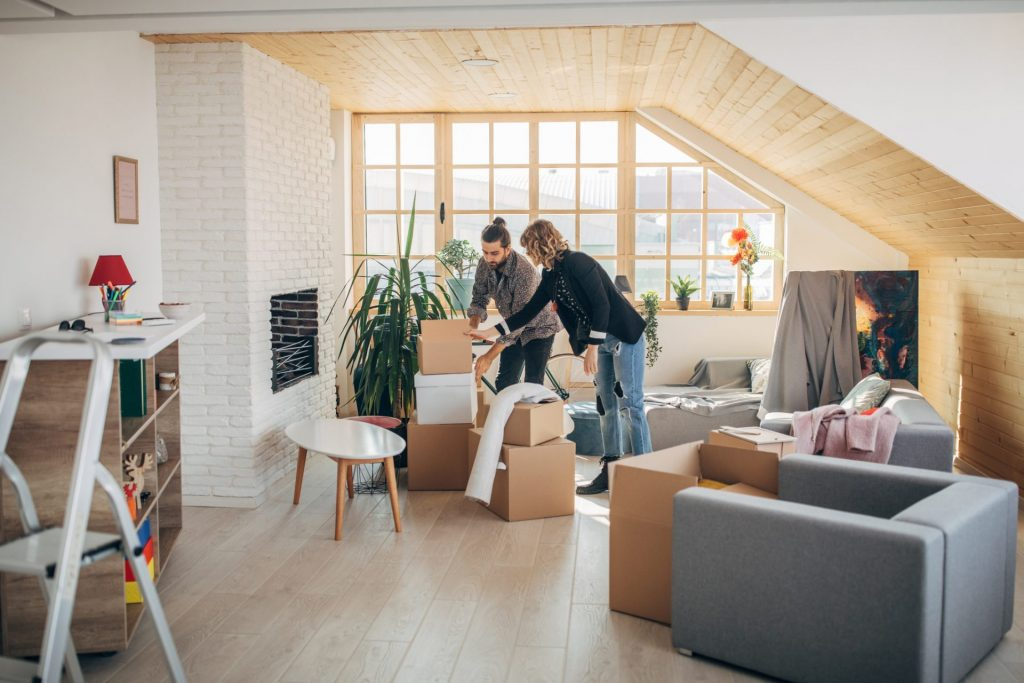 Man and woman, young couple moving into their new apartment together.