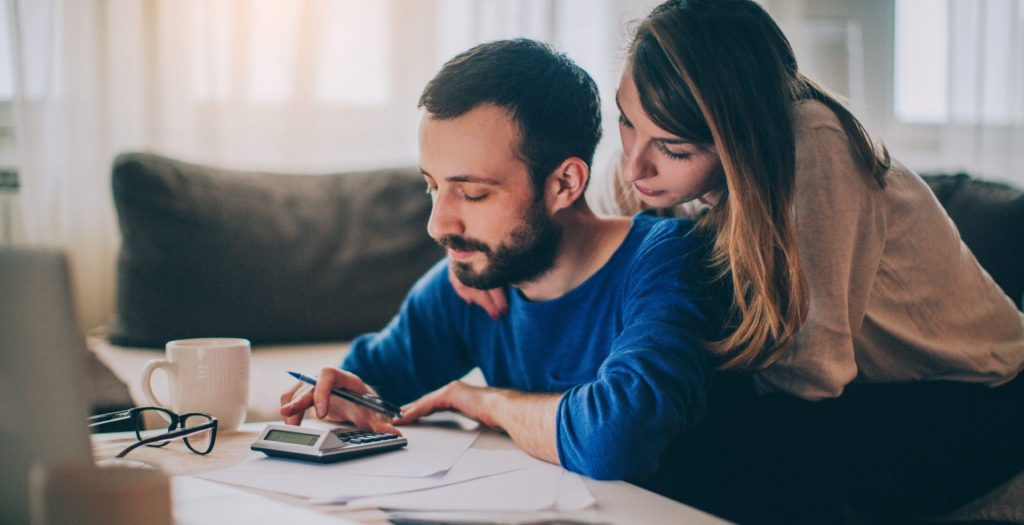 Couple sitting in their living room and checking their finances