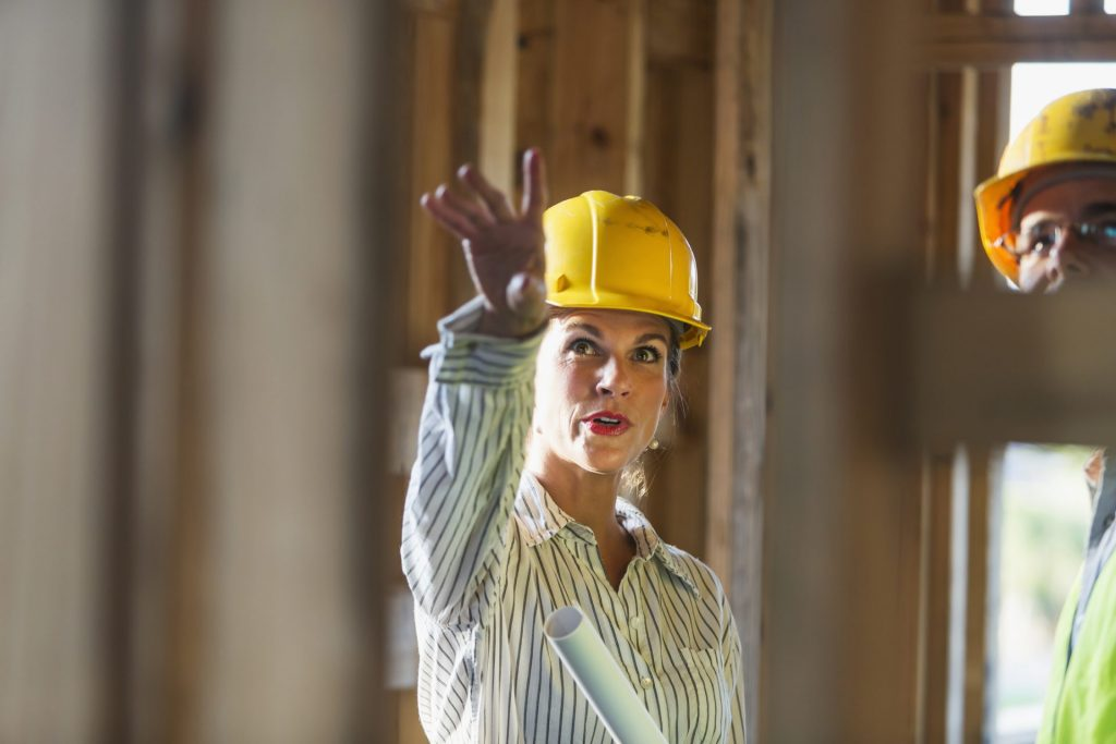 Two workers talking at a construction site, standing in a building in the framing stage.  The focus is on the mature woman, wearing a yellow hard hat, holding a set of rolled-up plans, pointing upward.  The male worker is cropped and partly obsured by the wooden frame.