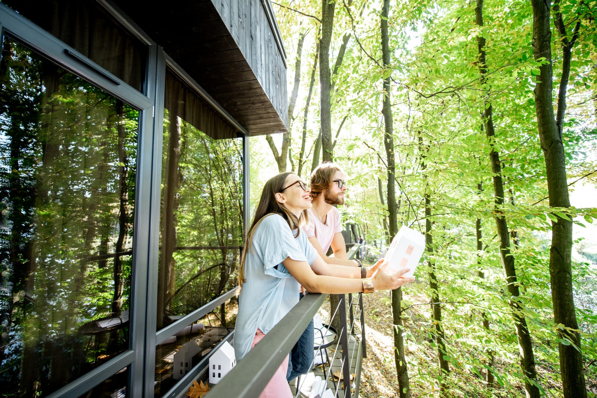 Young creative couple standing with house model on the balcony, designing or dreaming about eco houses in the forest