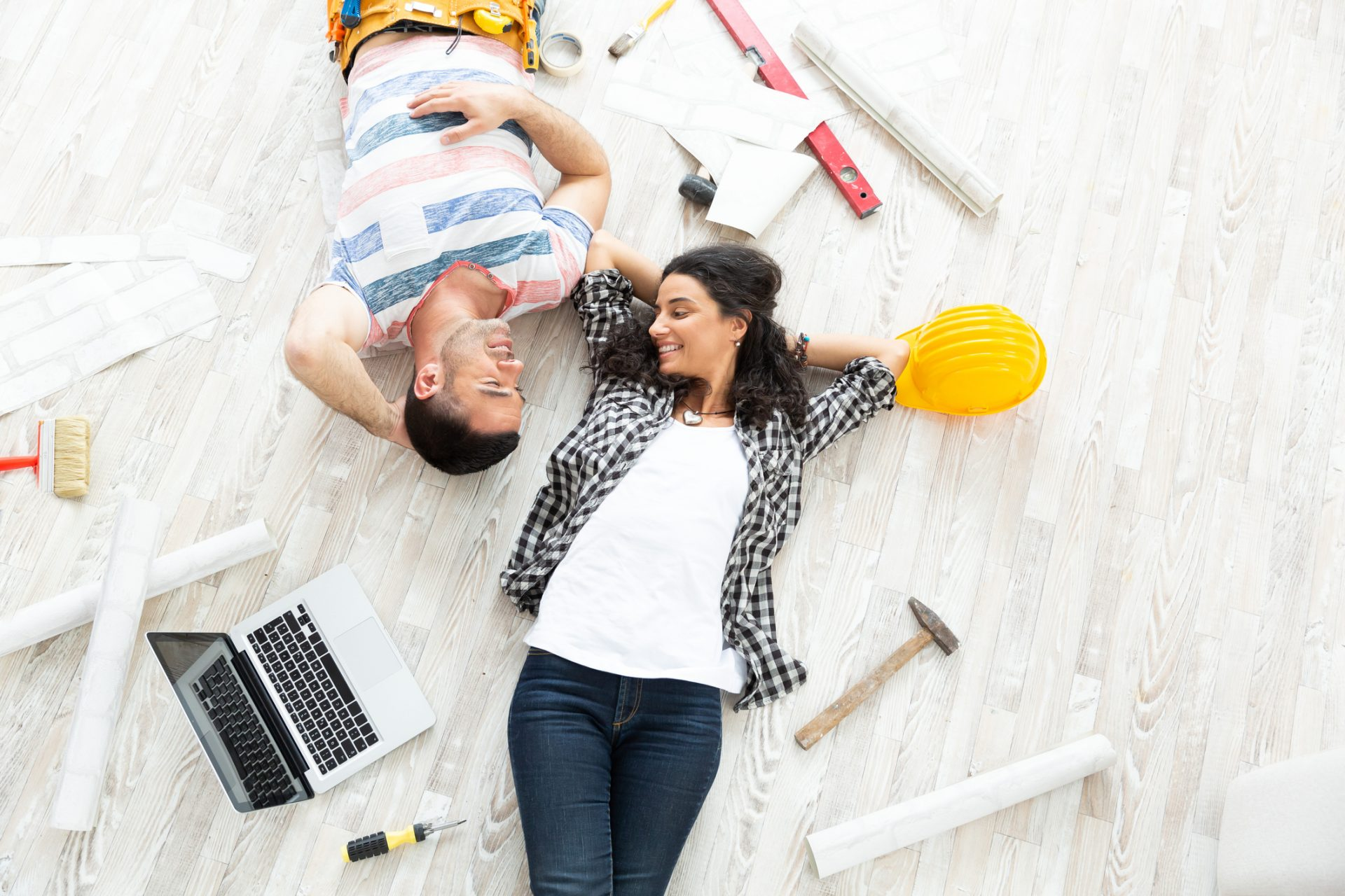 Couple making home improvement, lying down on floor, high angle view.