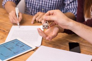 Happy young couple getting keys of their new house. Close up of female hand receiving keys from house broker. Closeup of the hand of a real estate agent who give the house keys to a woman while her boyfriend signing a contract.