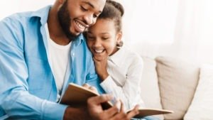 Father and daughter reading book together, sitting on sofa at home